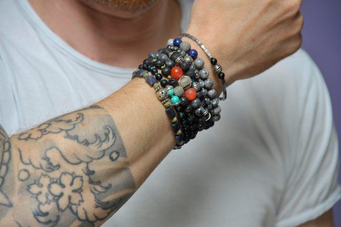 bracciali con pietre dure, su braccio uomo tatuato, pietre colorate
